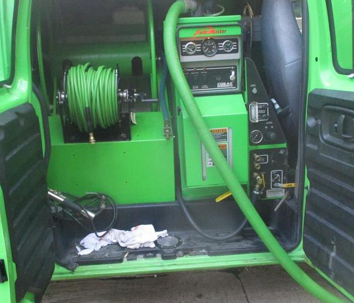 inside of green van with green equipment, cords and hoses