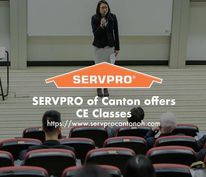 Orange SERVPRO  house logo on image with teacher in a classroom.